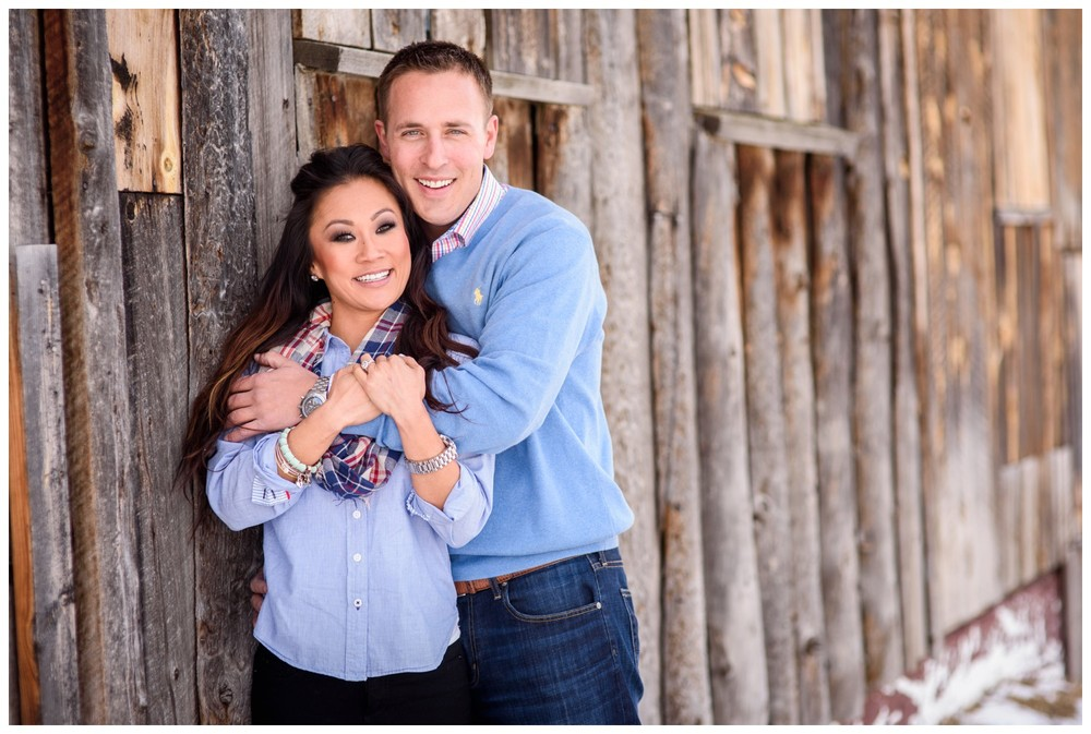 engaged couple smile while leaning against rustic barn in Evergreen colorado
