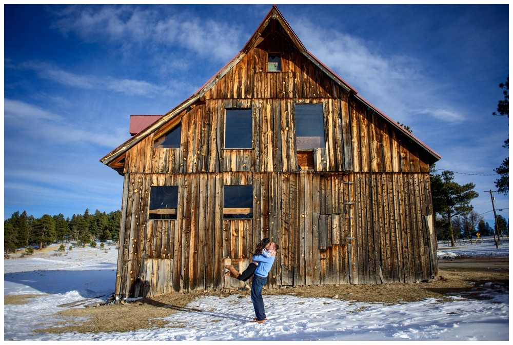 man lifts fiance in front of wood barn engagement photo