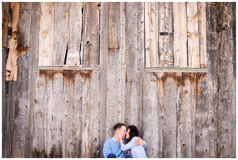 couple kiss in front of large wood barn at three sisters park