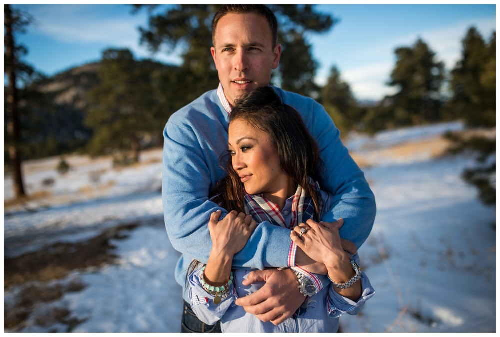 couple hug in sunny winter Colorado engagement photo