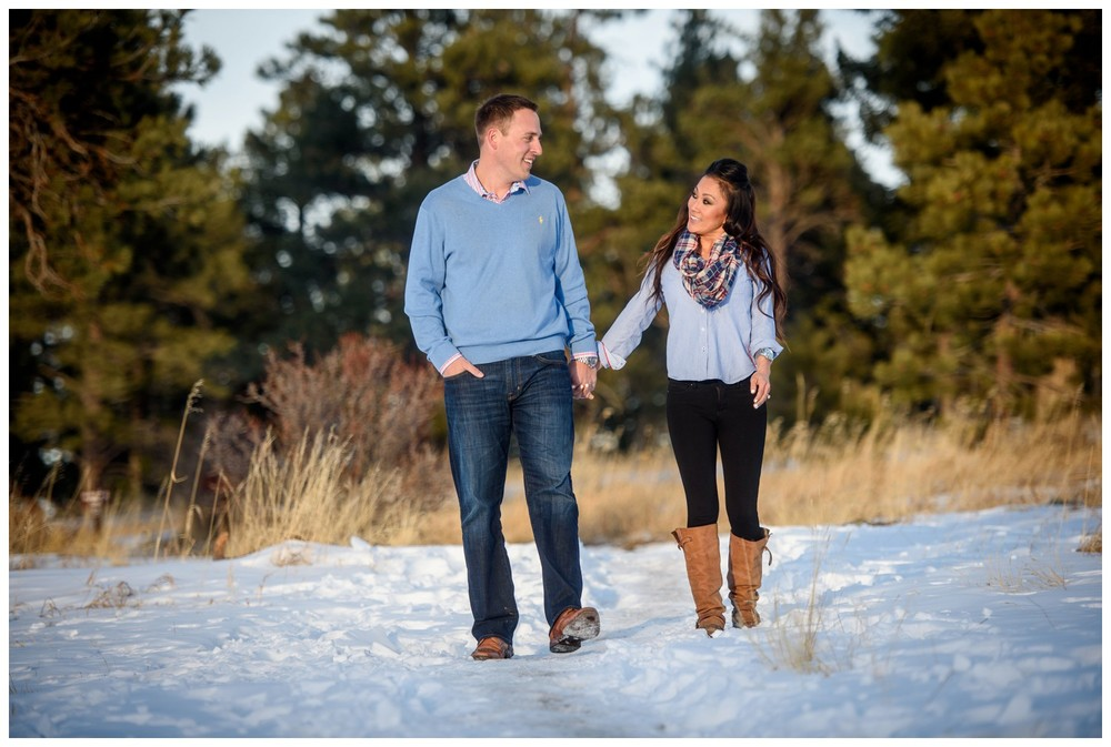 Colorado engaged couple walk through snow holding hands