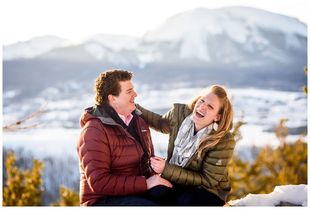 couple laughs on winter mountain top