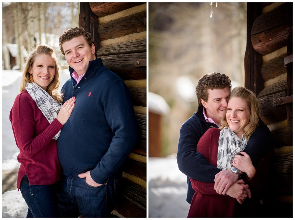 engaged couple laugh against colorado wood barn