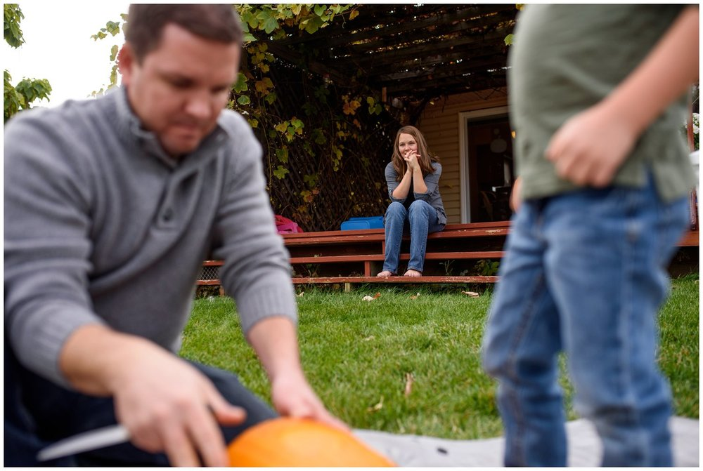 mother watches family carve pumpkins in greeley documentary family photo