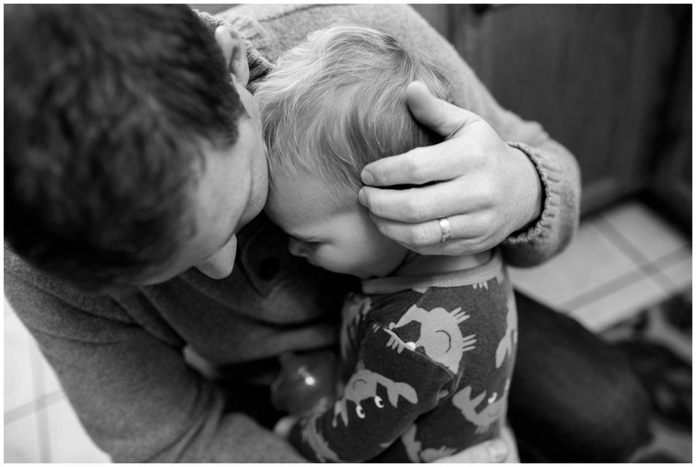father hugs son black and white photo