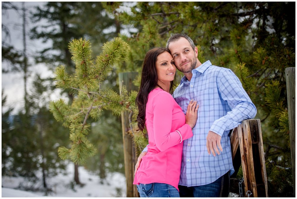 couple smiles and leans on wooden fence in Colorado mountains