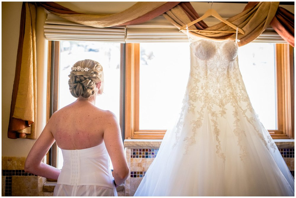 colorado bride looks at wedding dress in window
