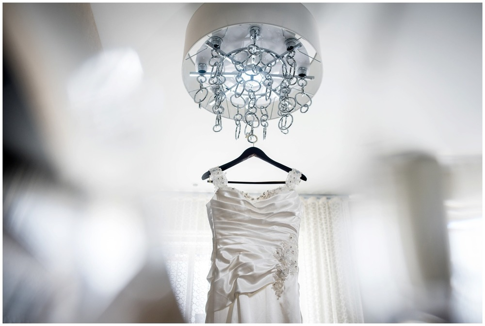 wedding dress hangs from chandelier