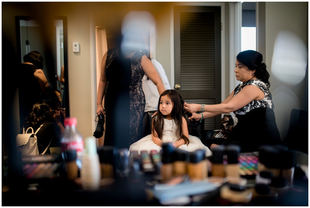 cute flower girl getting hair done in hotel room