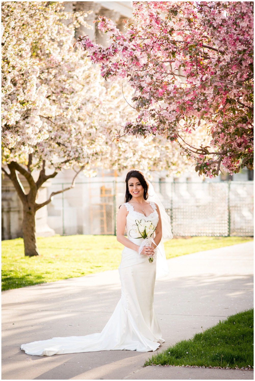 Latin Bride standing under apple blossom trees