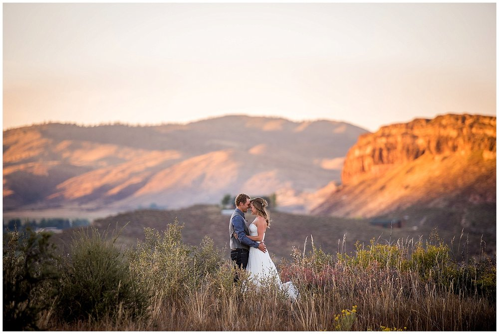 wedding couple on mountain overlook at sunset