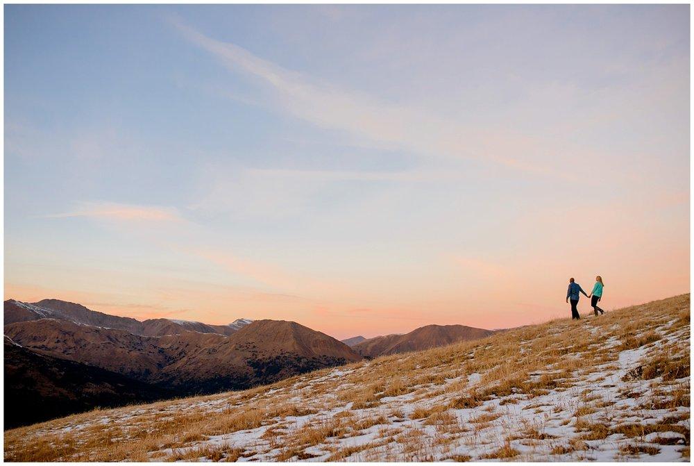 couple walks on Loveland Pass at Sunset