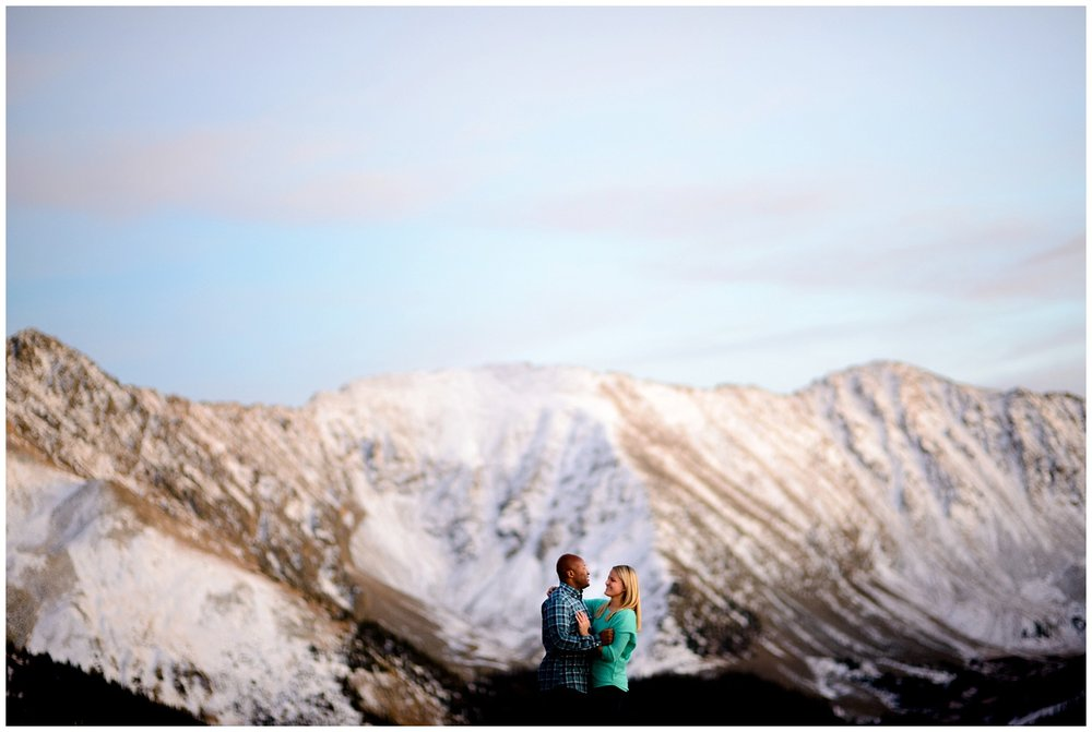 mountain top winter engagement photo at sunset