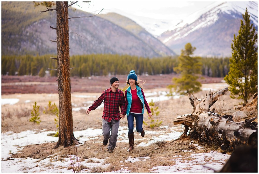 engaged couple runs in Colorado mountains
