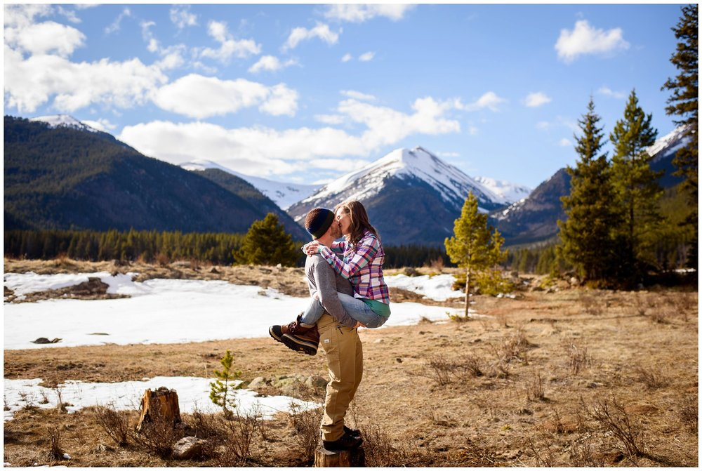 couple kisses in front of epic Colorado mountains
