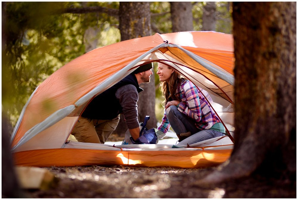 engaged couple laugh behind tent at campground