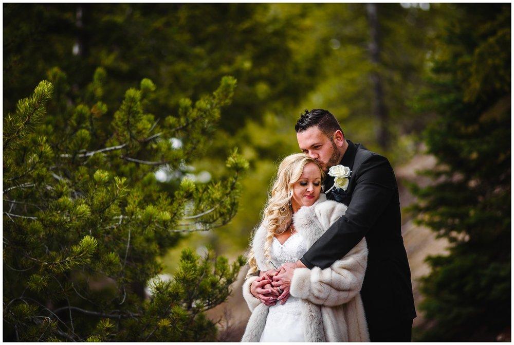 Bride and groom hug on mountain