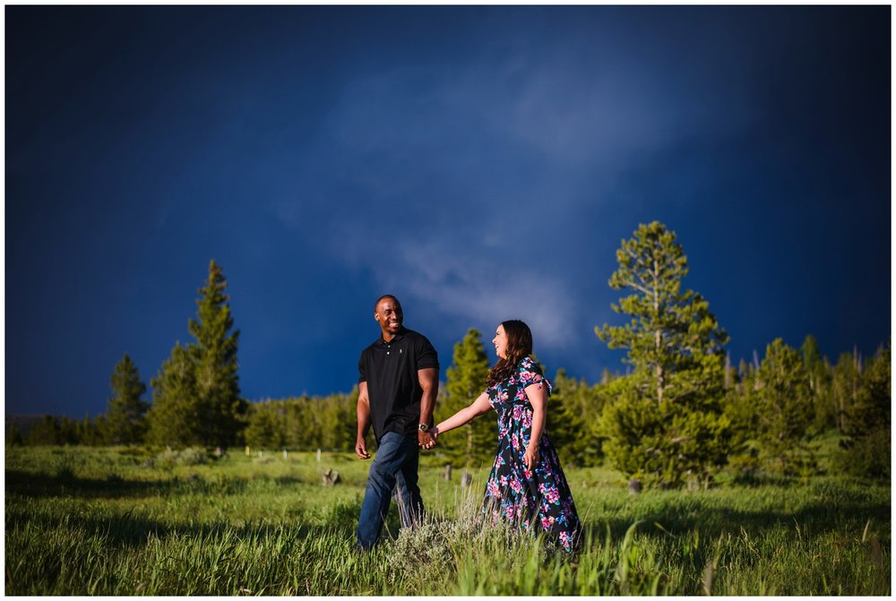 candid engagement photo mountain meadow near breckenridge