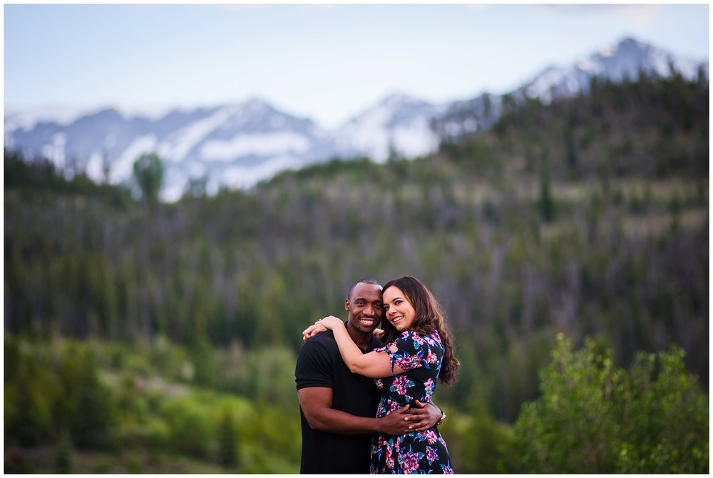 couple hugs in front of Breckenridge mountains