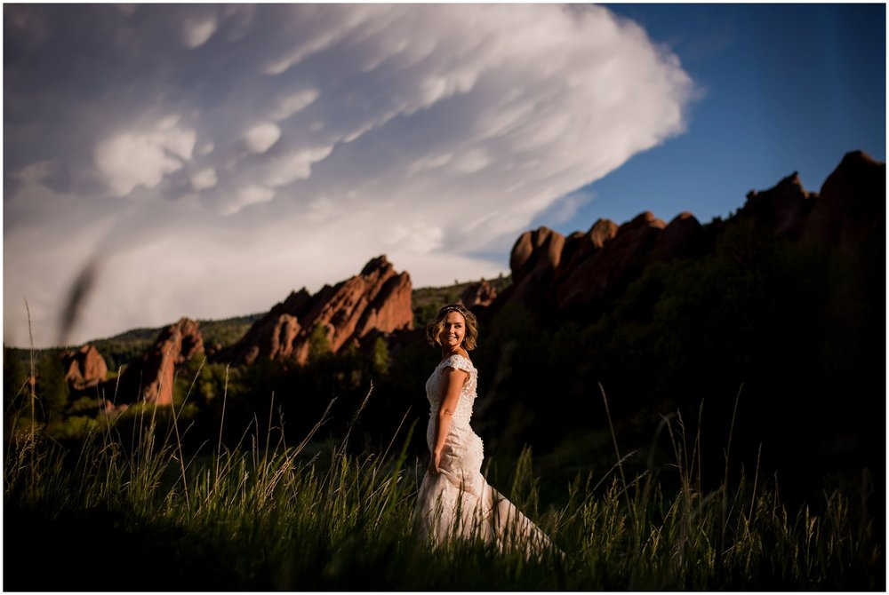 colorado bride poses in front of huge clouds