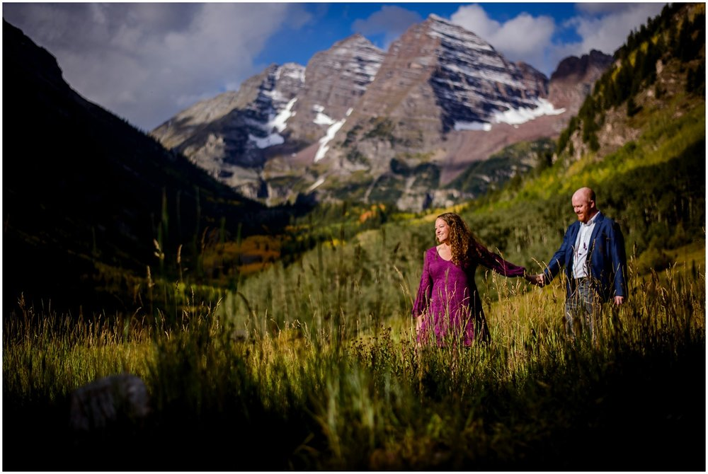 couple walks through field at Maroon Bells