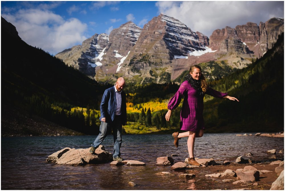 couple walks over lake rocks at Maroon Bells