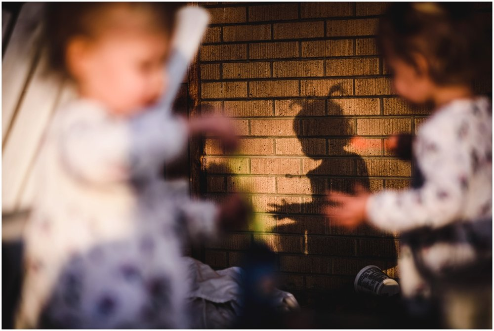 backyard shadow of twin girls in candid photo