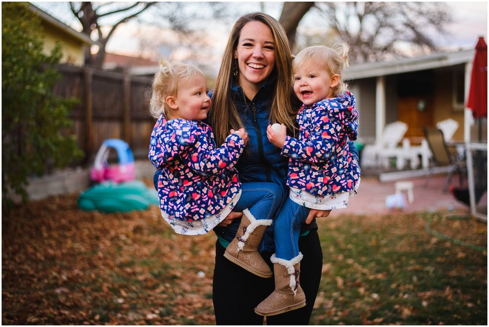 mom holds twin girl toddlers