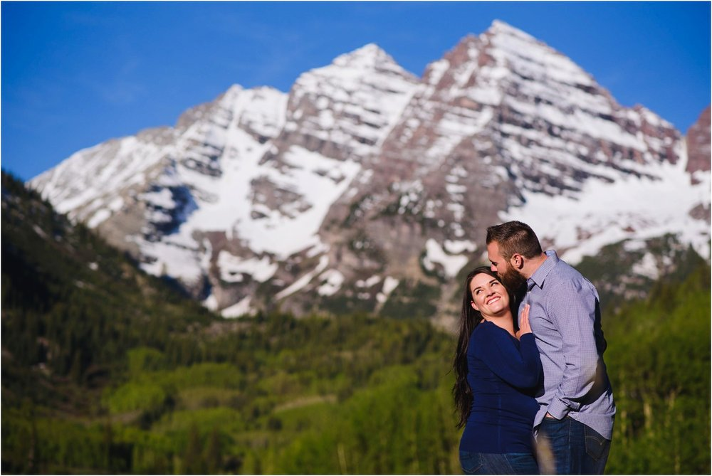 Engaged couple laughs in front of Maroon Bells