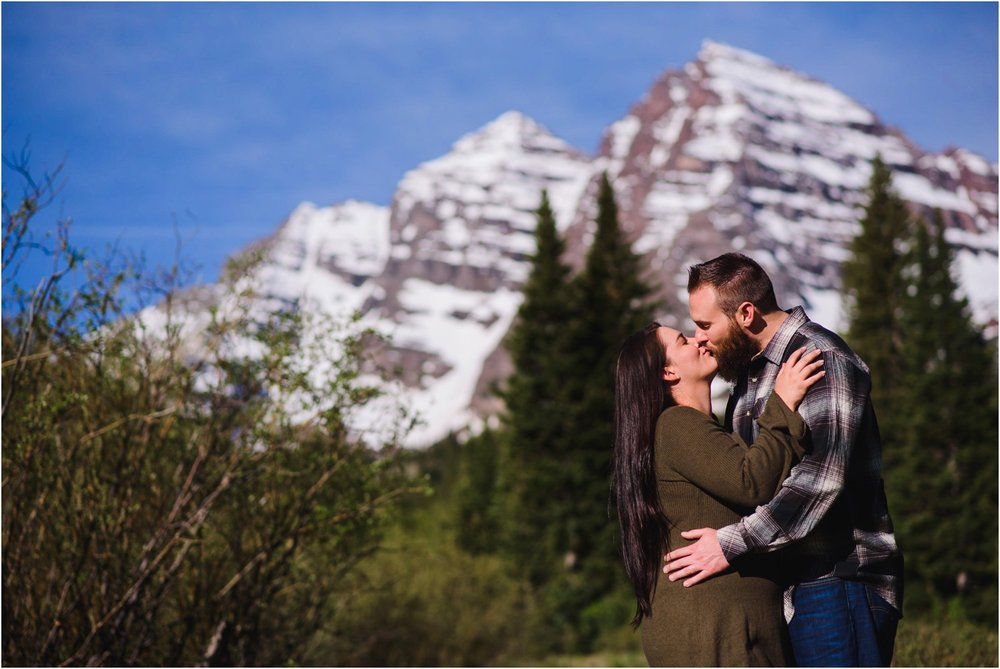 Couple kisses in front of Maroon Bells