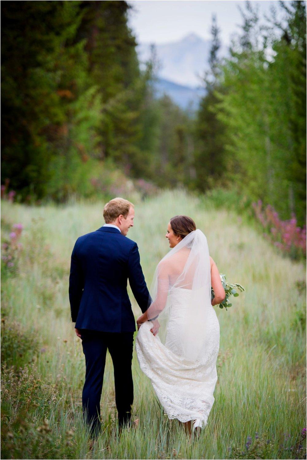 Bride and Groom walk in meadow in Keystone colorado