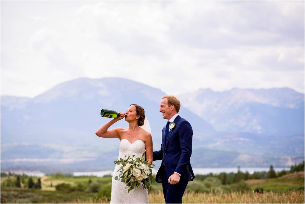 Bride drinks champagne on mountain