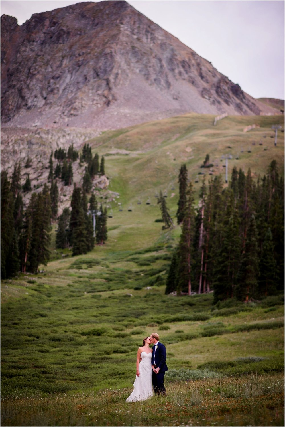 Bride and groom kiss on top of Colorado mountains