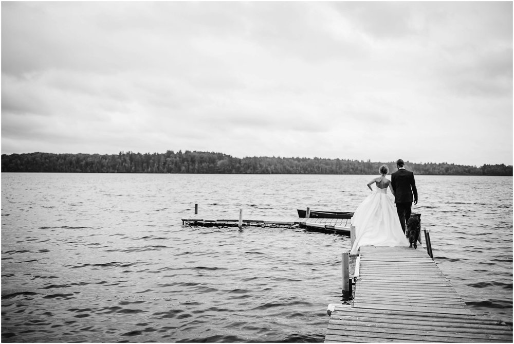Bride and Groom walk on lake dock
