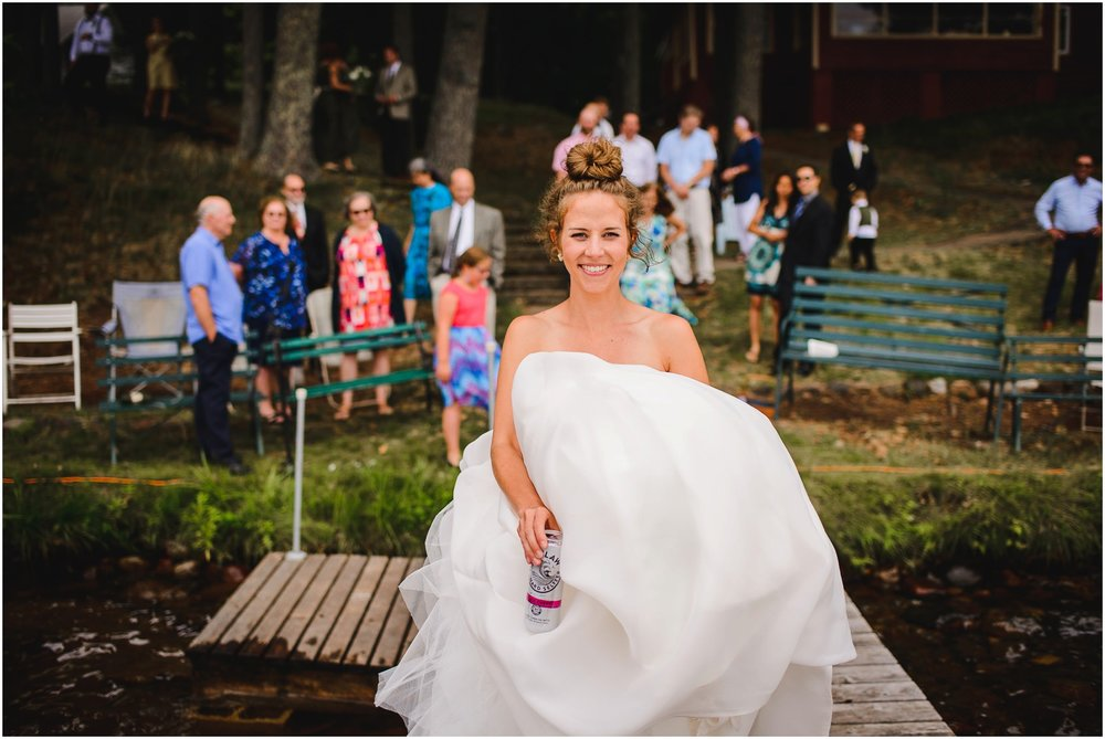 bride drinking White Claw drink on Dock
