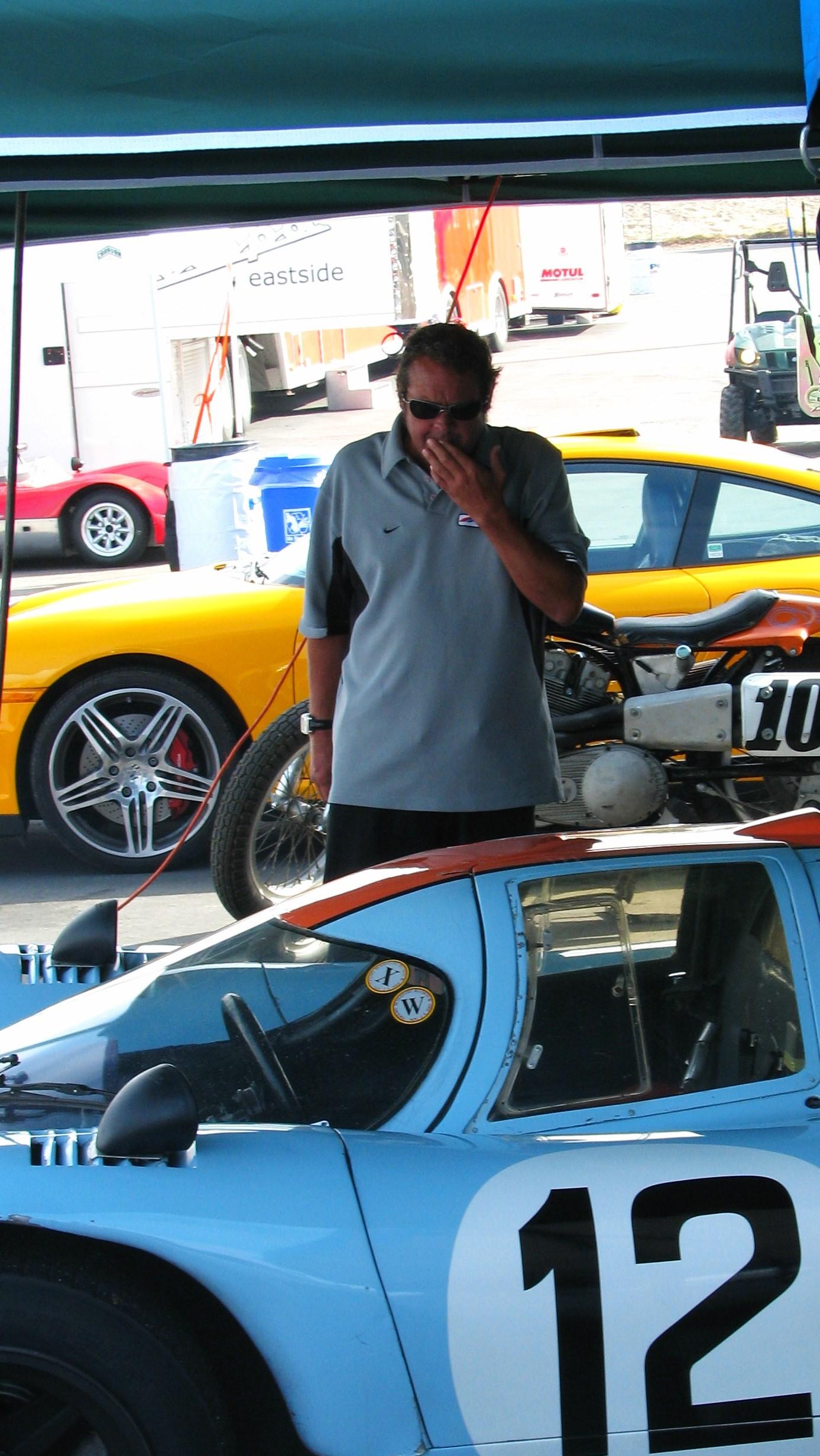 Chad McQueen admires a Porsche 917K in the paddock.