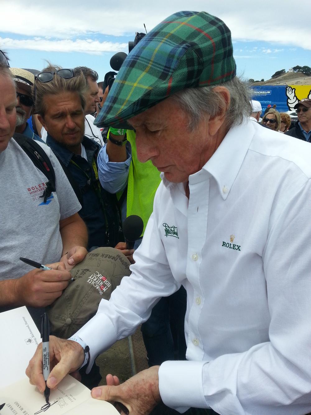 Sir Jackie Stewart signs autographs