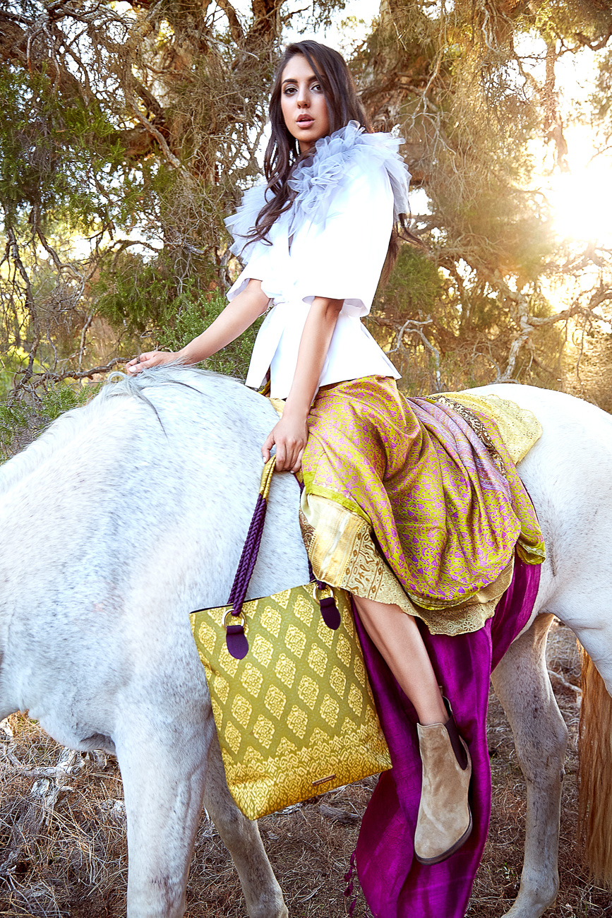 Yellow handbag with intricate pattern detail and fuchsia pink silk scarf