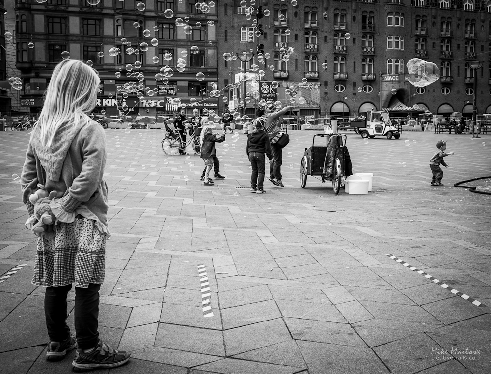 young girl in Copenhagen, Denmark standing in a square watching bubbles drift past.