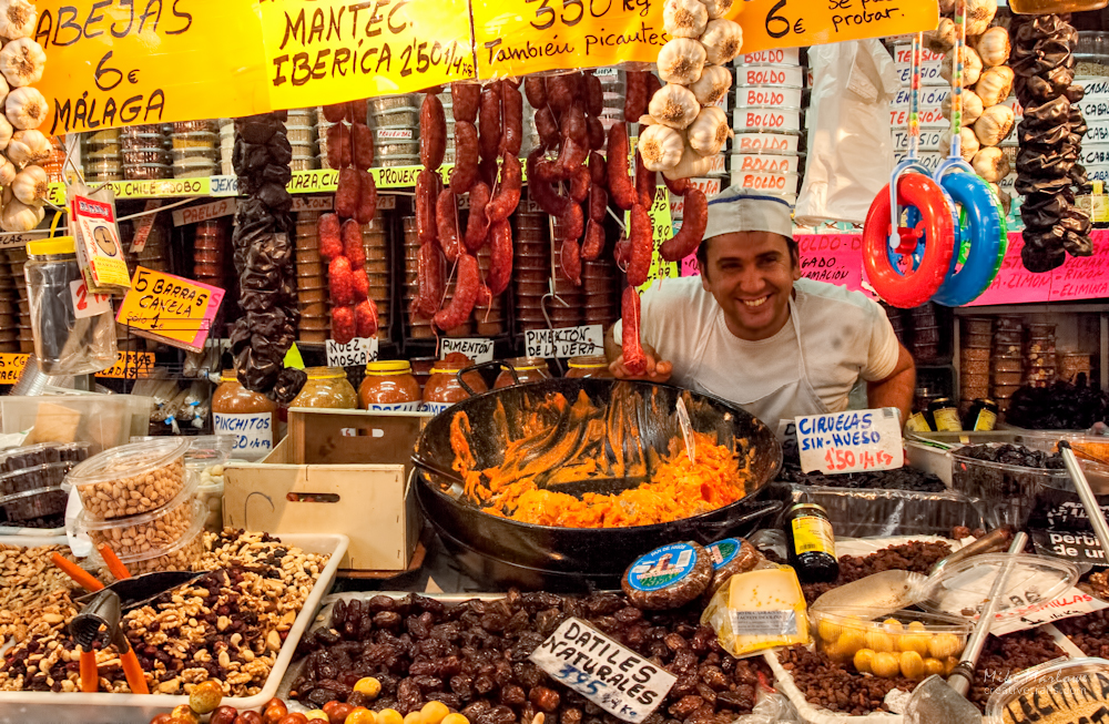 A shopkeeper in at a market in southern Spain selling meat, dried fruit and nuts.