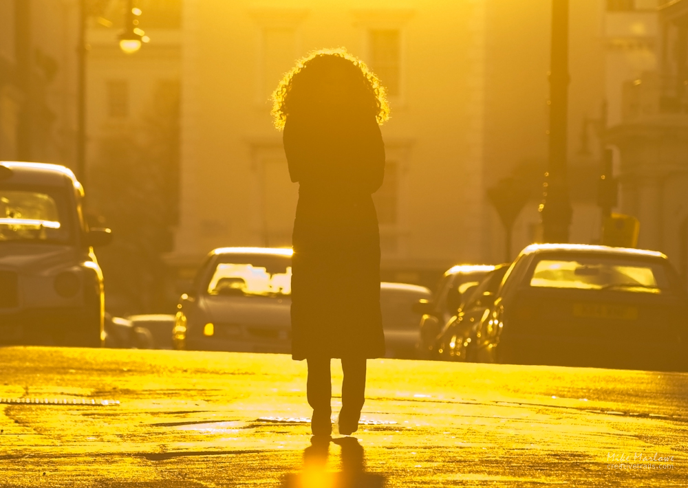 Woman walking along street in London at dusk with warm backlit feel. Photograph Mike Marlowe. No commercial use permitted.