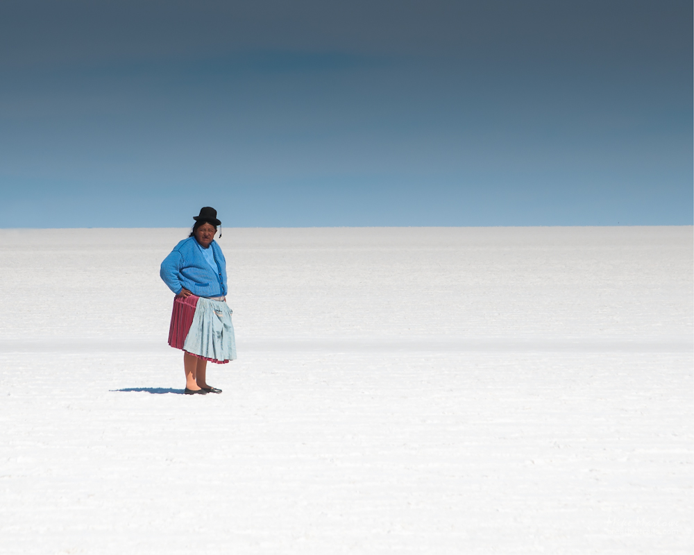 A portrait of a woman staring into the camera on the Salt Flats of BOlivia