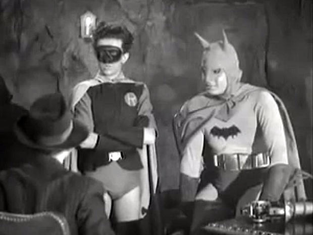 Batman and Robin interrogate a captured thug in the Bat's Cave.