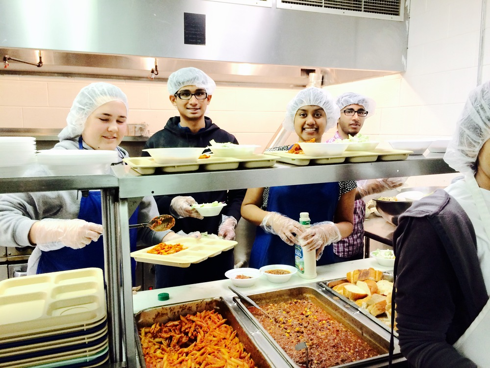 Meghana (second from right) serves up dinner at Open Door Ministries to more than 100 low-income and homeless community members.