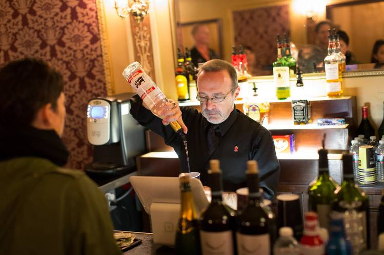 Bartender Paul A. Brown pours a drink in the Winter Garden Theatre during a performance of 'School of Rock.'PHOTO:AGATON STROM FOR THE WALL STREET JOURNAL