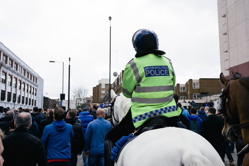 Police on horses keep the boisterous fans in check.