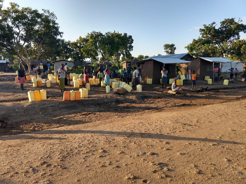 Refugees waiting with jerry cans for the water truck to arrive to get their daily water supply