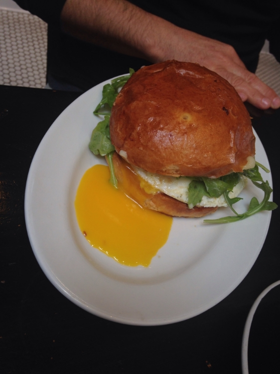 FRIED EGG SANDWICH over easy egg, Canadian bacon, jack cheese & arugula dressed with garlic aioli on a toasted brioche bun.