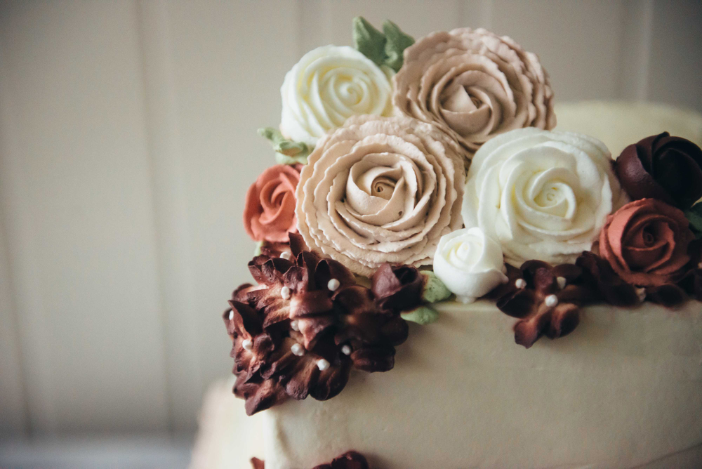 Three layers of mocha kahlua cake with dusty pink ruffles on the base and groups of cascading roses and hydrangeas