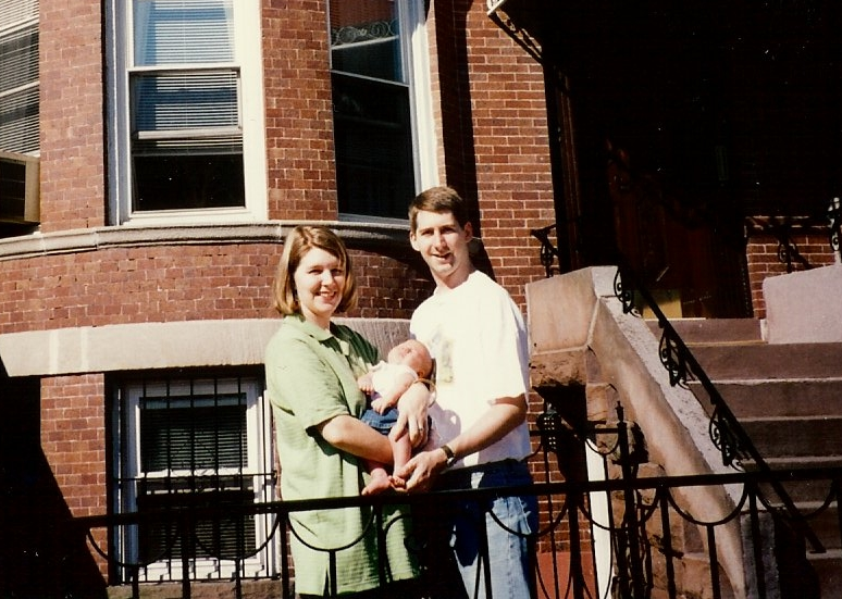 My mom and dad standing with me in front of our apartment, 1997